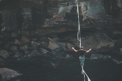 A tightrope walker crosses a gorge