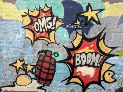 """Graffiti with stars and grenades, saying """"OMG!"""" and """"Boom!"""""""